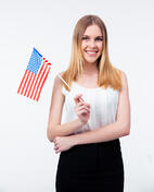 Happy young businesswoman standing with US flag over gray background and looking at camera