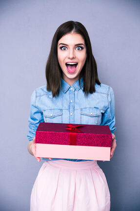 Surprised woman holding gift and looking on camera over gray background