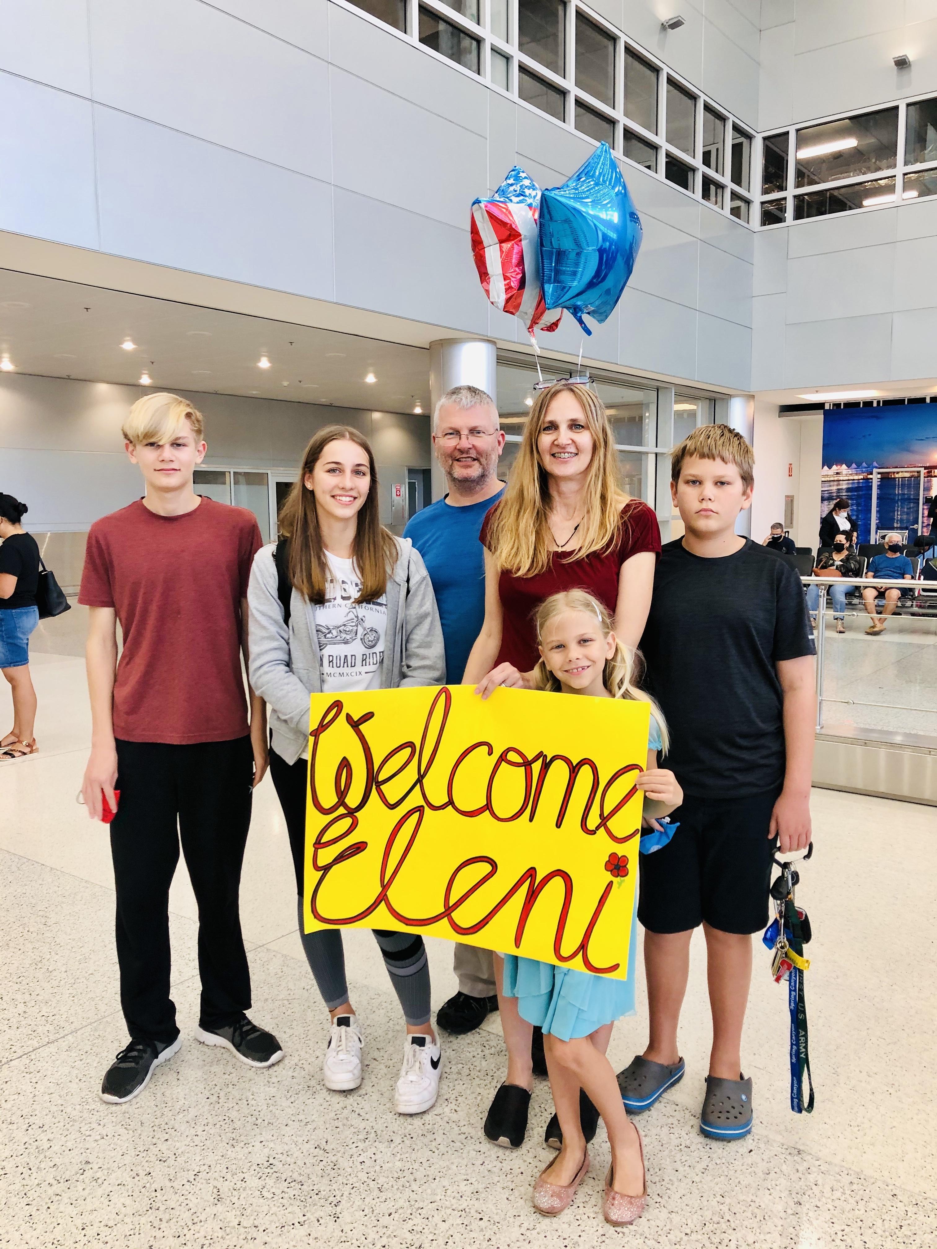 Gastfamilie empfängt Teilnehmerin am Flughafen mit großem bunten Plakat