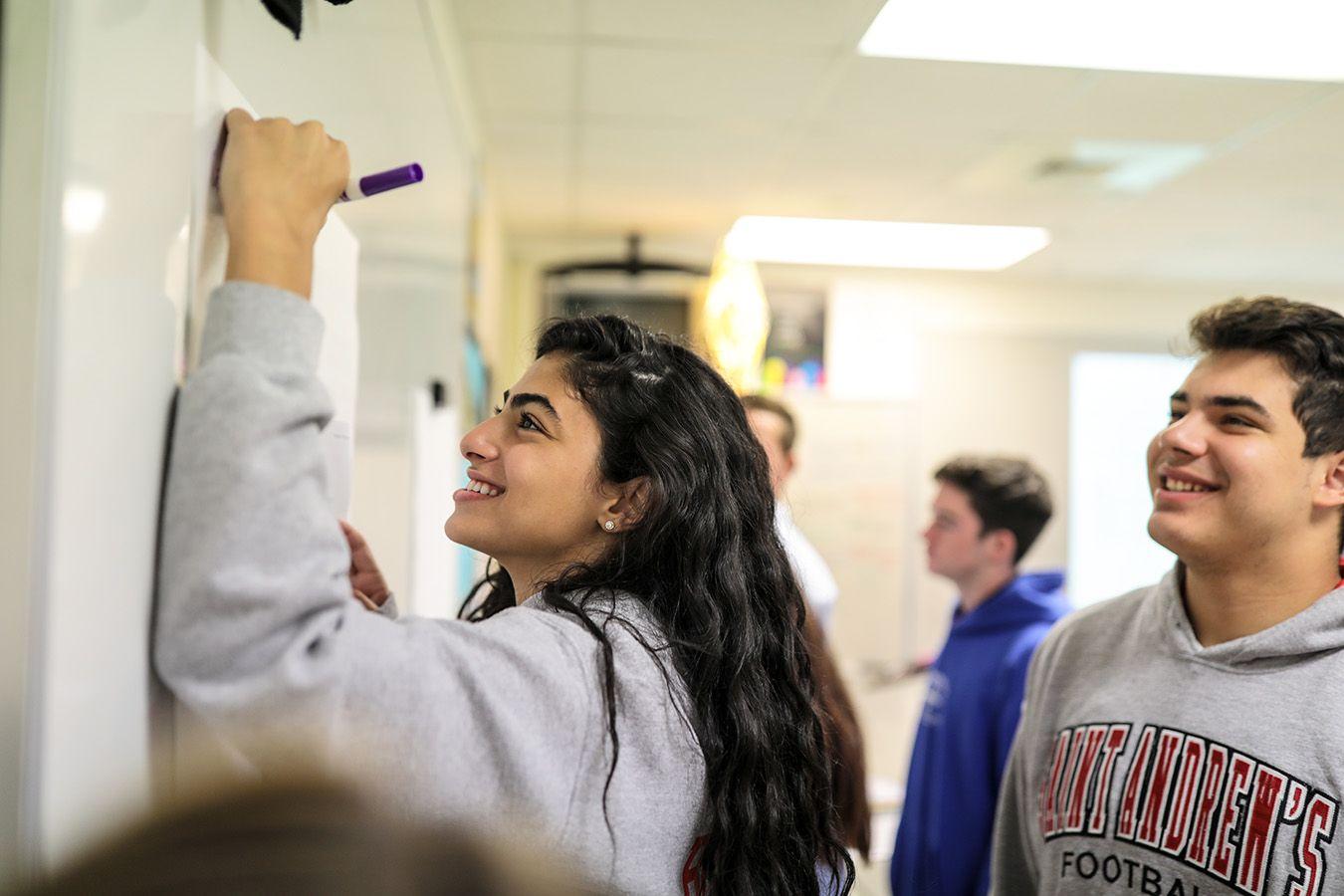 Eine Schülerin schreibt etwas an ein Whiteboard