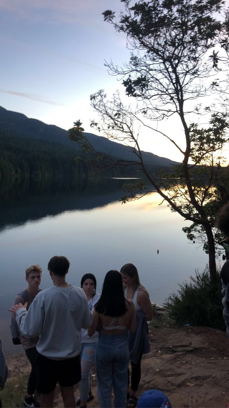 Gruppe von Jugendlichen am See bei Sonnenuntergang