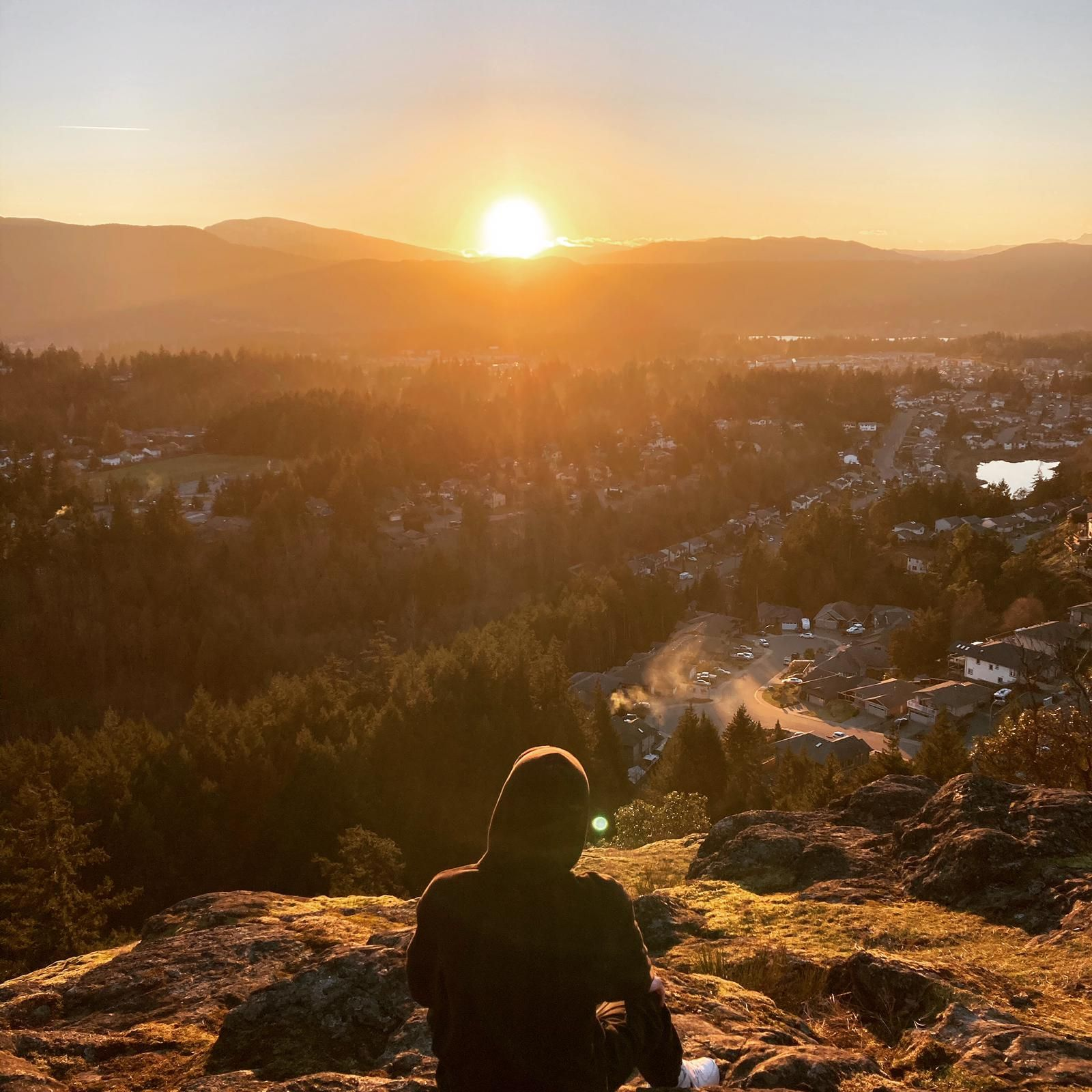 Teilnehmer sitzt auf einem Berg während dem Sonnenuntergang