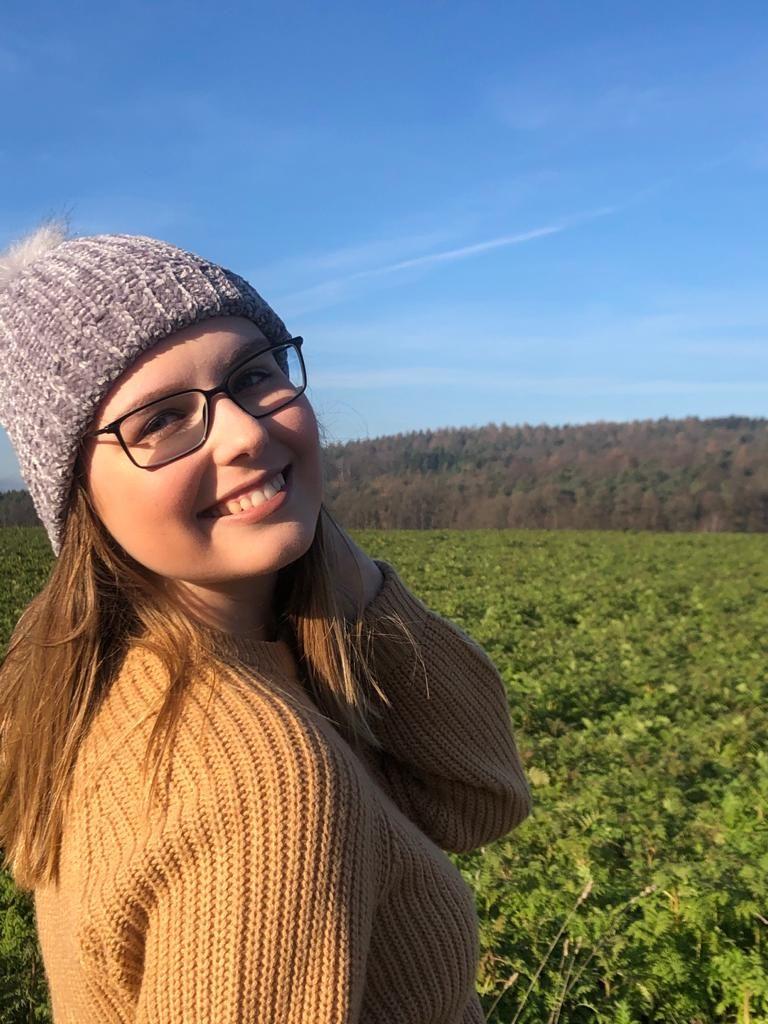 Teilnehmerin vor grünem Feld lächelt über Schulter